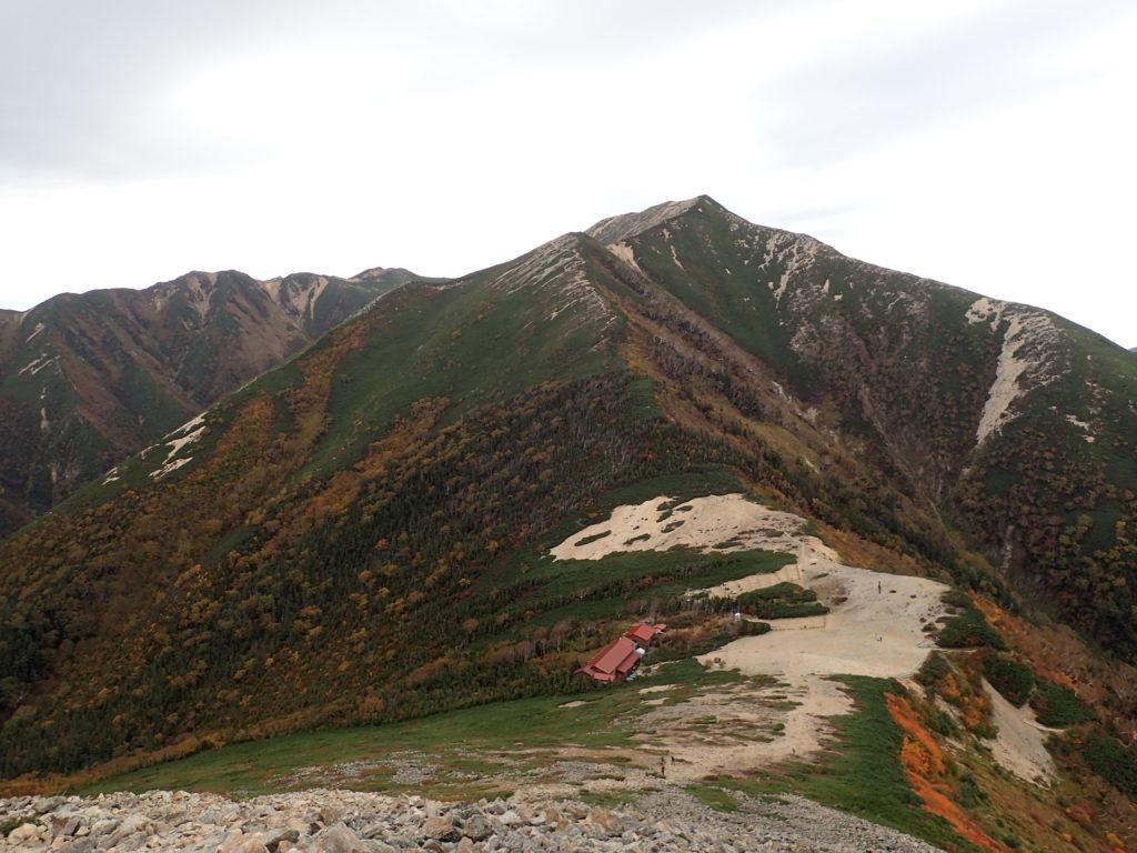 常念岳の山頂方向から見おろす常念小屋と横通岳