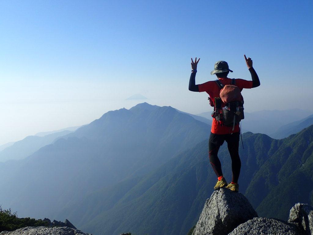 甲斐駒ヶ岳山頂で鳳凰三山と富士山を背景に記念撮影
