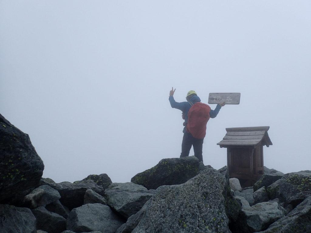 雨の槍ヶ岳山頂でモンベルの登山用レインウェアであるトレントフライヤーを着て記念撮影