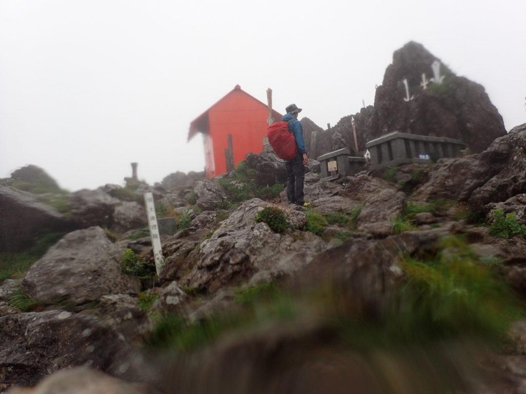 大雨の早池峰山頂でモンベルの登山用レインウェアであるトレントフライヤーを着て記念撮影