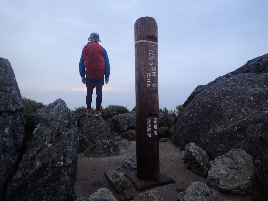 屋久島の宮之浦岳山頂でモンベルの登山用レインウェアであるトレントフライヤーを着て記念撮影