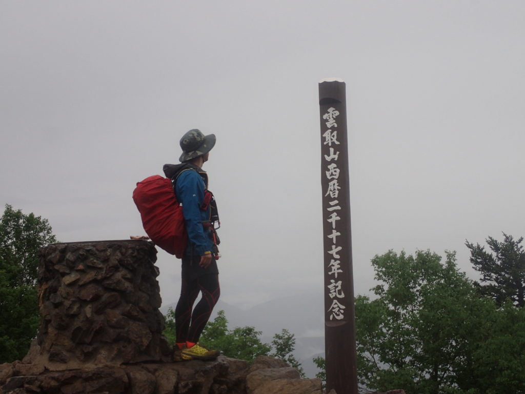 雨の雲取山山頂でモンベルの登山用レインウェアであるトレントフライヤーを着て記念撮影