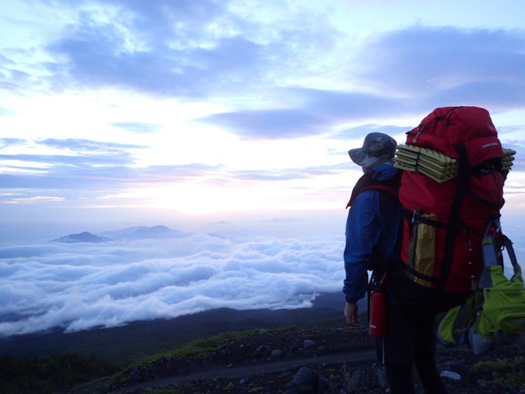 早朝で気温の低い富士山6合目でモンベルの登山用レインウェアであるトレントフライヤーを着て記念撮影