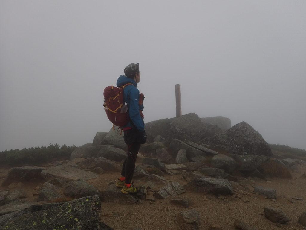 強風の双六岳山頂をモンベルの登山用レインウェアであるトレントフライヤーでしのぐ。