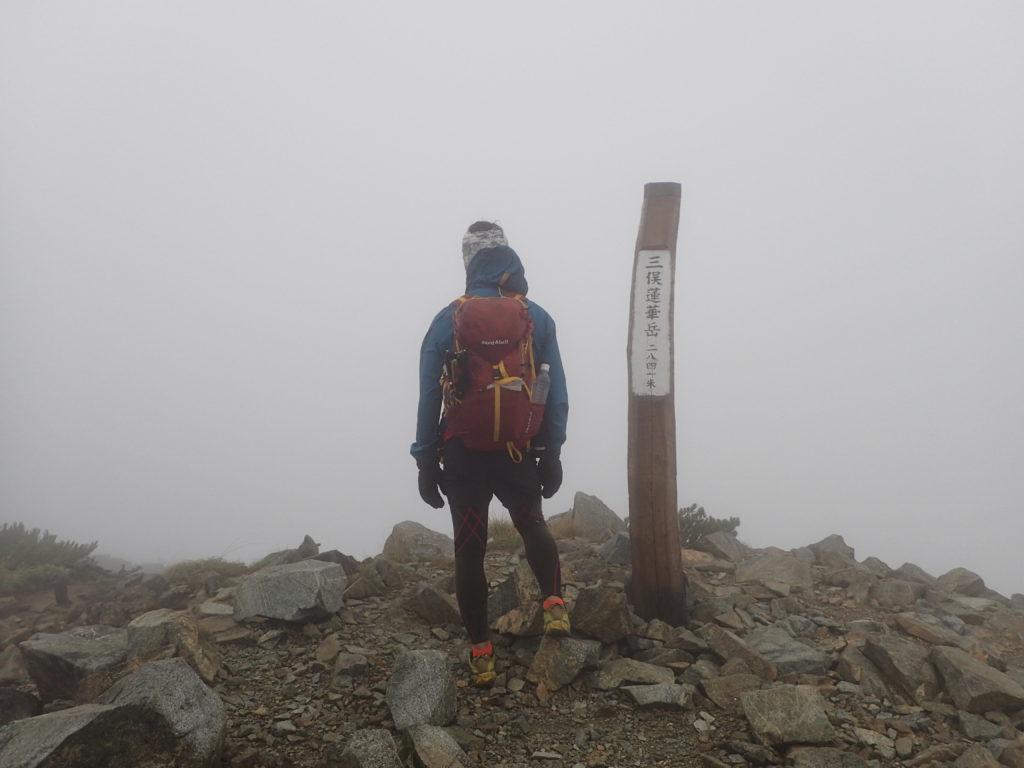 強風の三俣蓮華岳山頂をモンベルの登山用レインウェアであるトレントフライヤーでしのぐ。