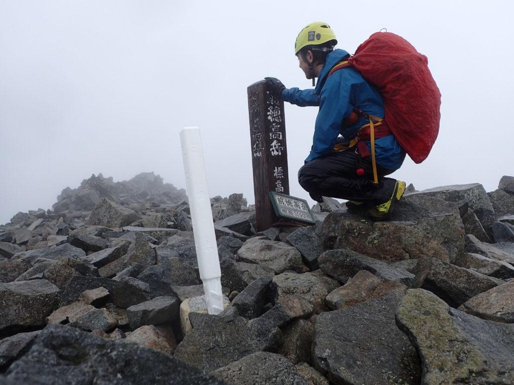 雨の前穂高岳山頂でモンベルの登山用レインウェアであるトレントフライヤーを着て記念撮影