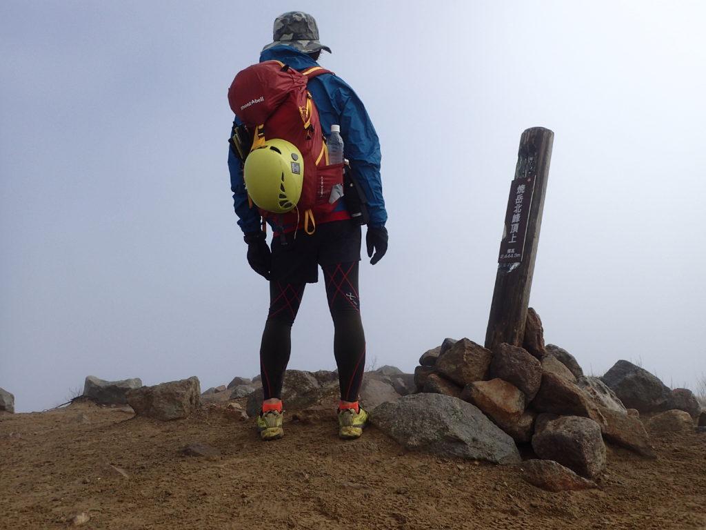 焼岳北峰山頂でモンベルの登山用レインウェアであるトレントフライヤージャケットを着て記念撮影