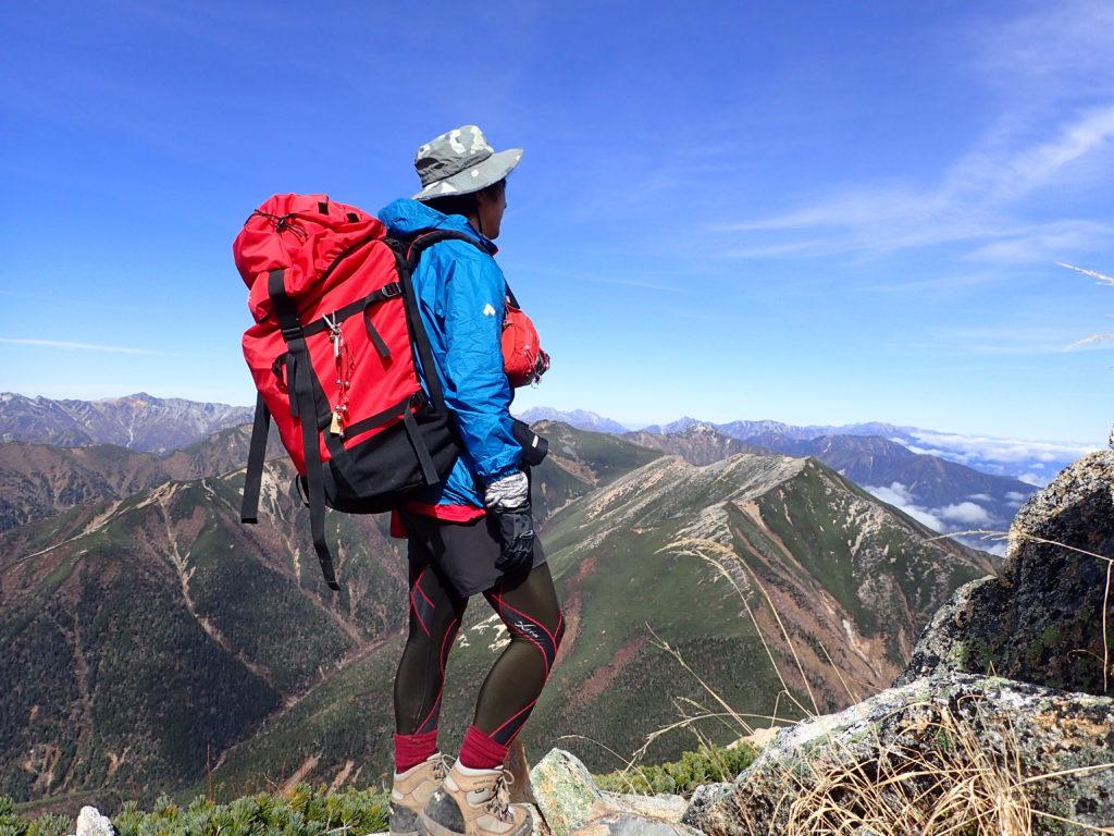 常念岳山頂でモンベルの登山用レインウェアであるトレントフライヤージャケットを着て記念撮影