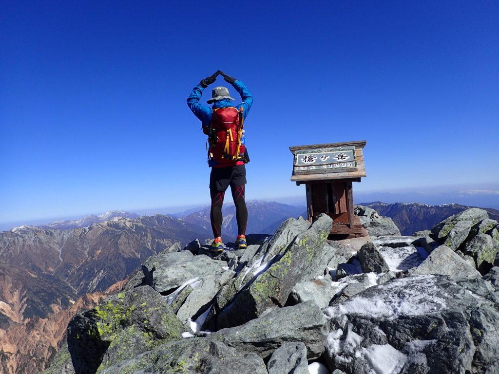 冷たい風が吹く北アルプスの槍ヶ岳山頂でモンベルの登山用レインウェアであるトレントフライヤーを着て記念撮影