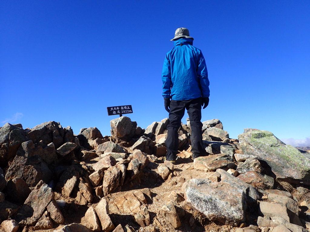 初冬で低温の大天井岳山頂でモンベルの登山用レインウェアであるトレントフライヤージャケットを着て記念撮影
