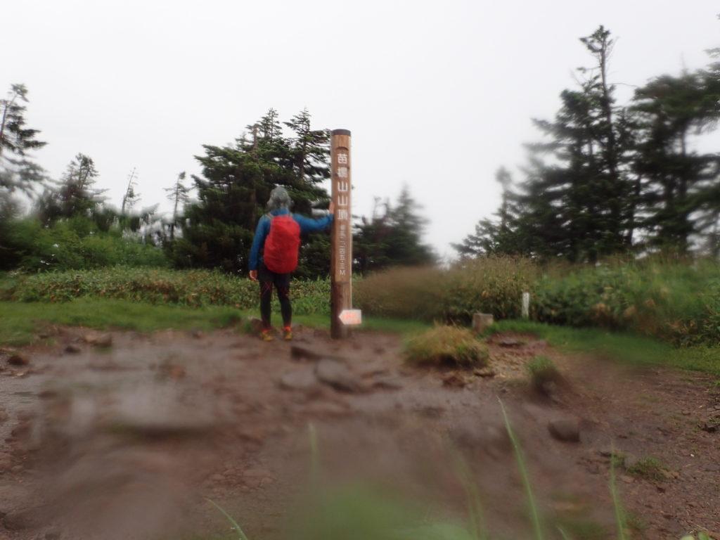 雨の苗場山山頂でモンベルの登山用レインウェアであるトレントフライヤーを着て記念撮影