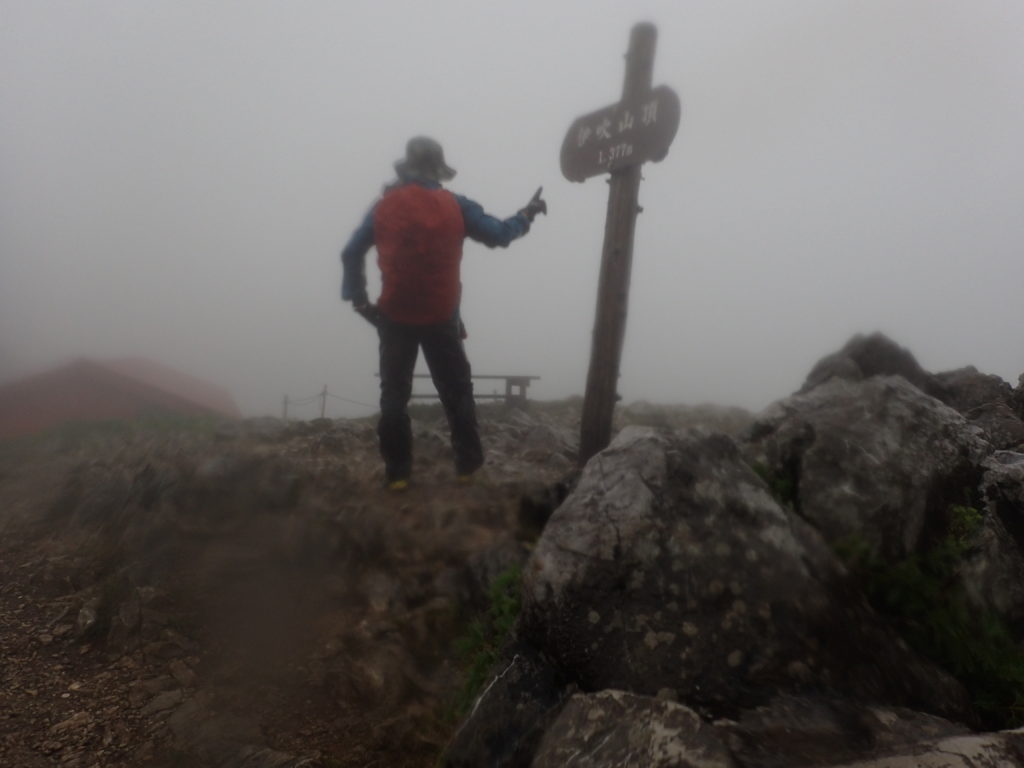 雨の伊吹山山頂でモンベルの登山用レインウェアであるトレントフライヤーを着て記念撮影