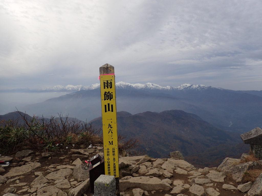 雨飾山の山頂標と北アルプス