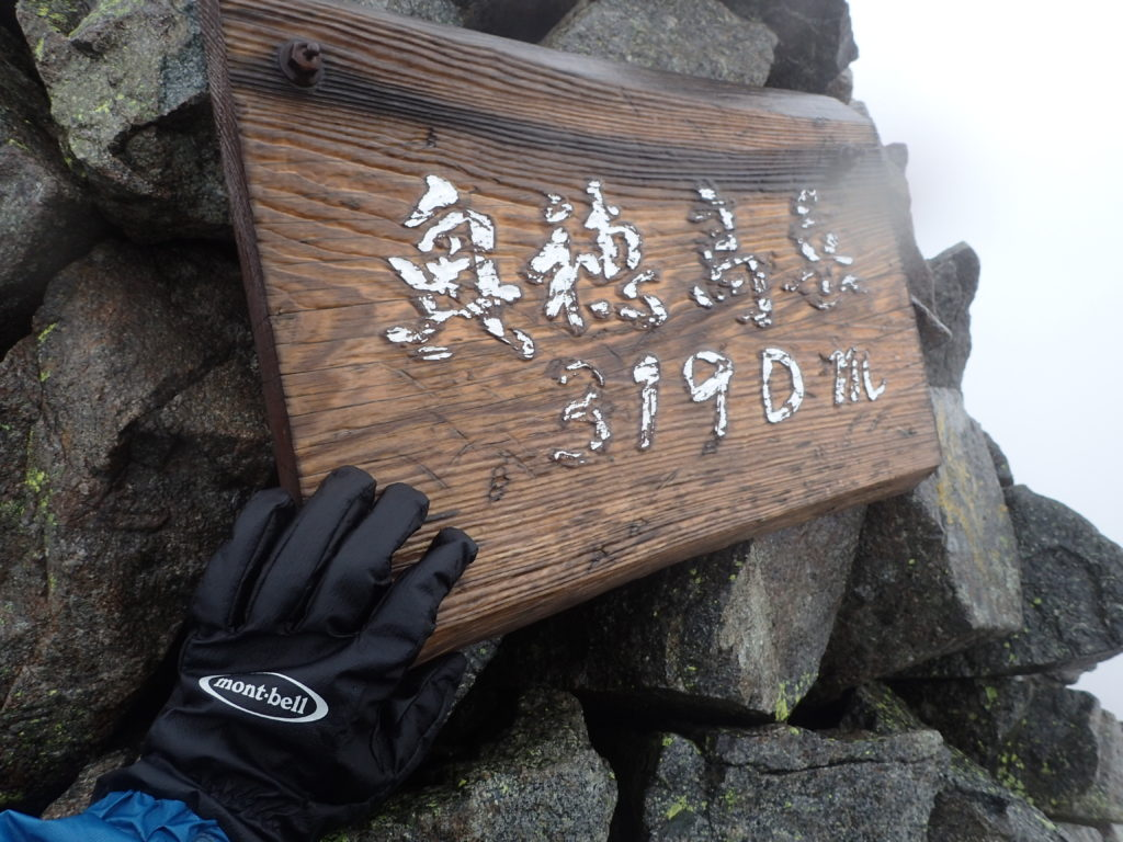 雨の奥穂高岳山頂でモンベルの登山用グローブであるサンダーパスグローブの記念撮影