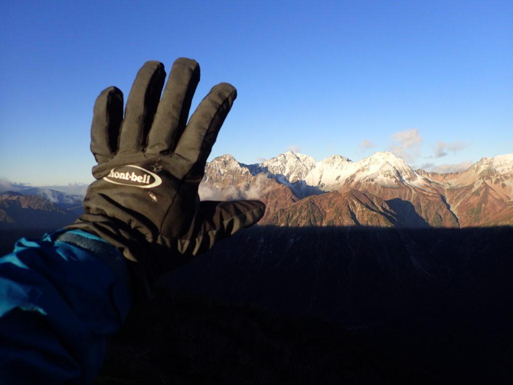 蝶ヶ岳の稜線で雪化粧をした穂高岳をバックにモンベルの登山用グローブであるサンダーパスグローブの記念撮影