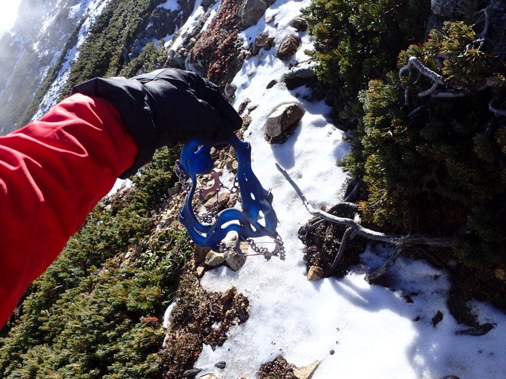 大天井岳の山頂直下で登山道に雪が着き始めたのでチェーンスパイクを装着準備