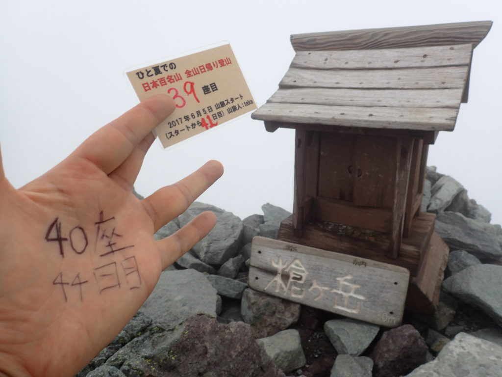 ひと夏での日本百名山全山日帰り登山で登った槍ヶ岳の山頂で自作の登頂カードで記念写真