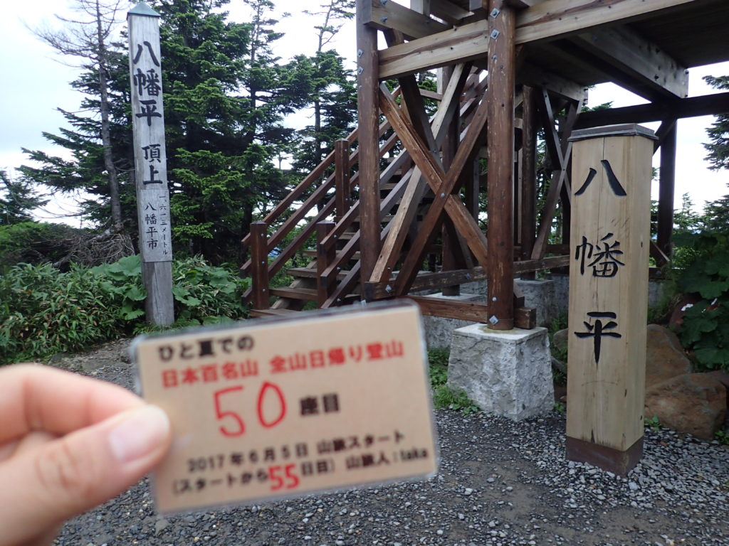 ひと夏での日本百名山全山日帰り登山で登った八幡平の山頂で自作の登頂カードで記念写真