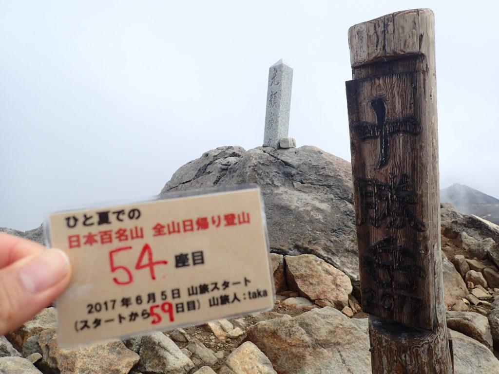 ひと夏での日本百名山全山日帰り登山で登った十勝岳の山頂で自作の登頂カードで記念写真