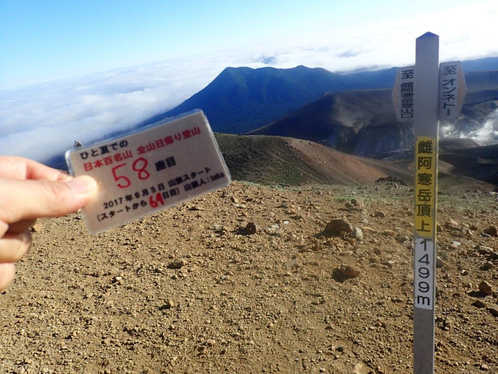 ひと夏での日本百名山全山日帰り登山で登った雄阿寒岳の山頂で自作の登頂カードで記念写真