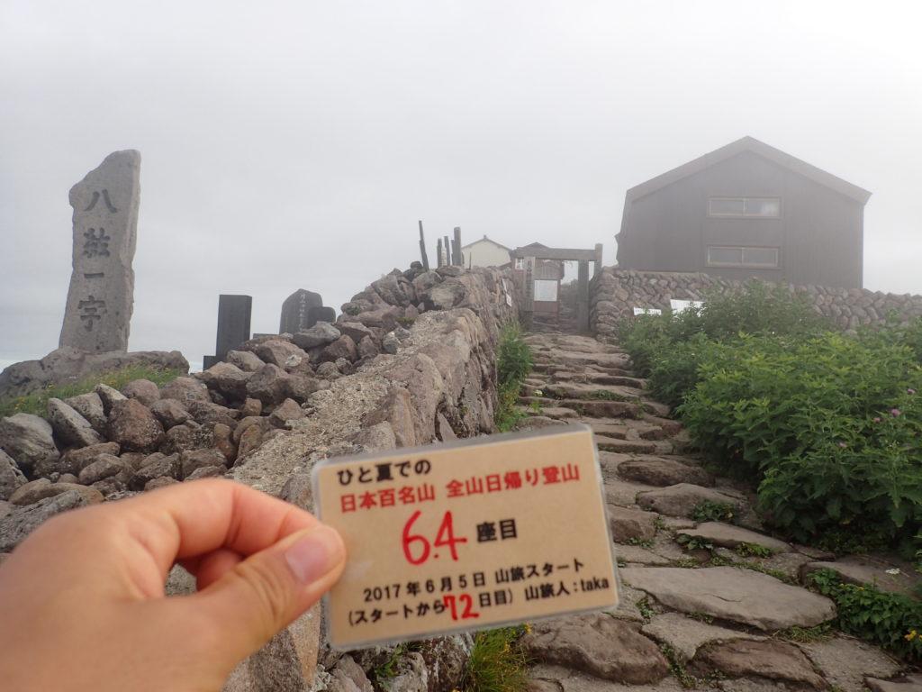 ひと夏での日本百名山全山日帰り登山で登った月山の山頂で自作の登頂カードで記念写真
