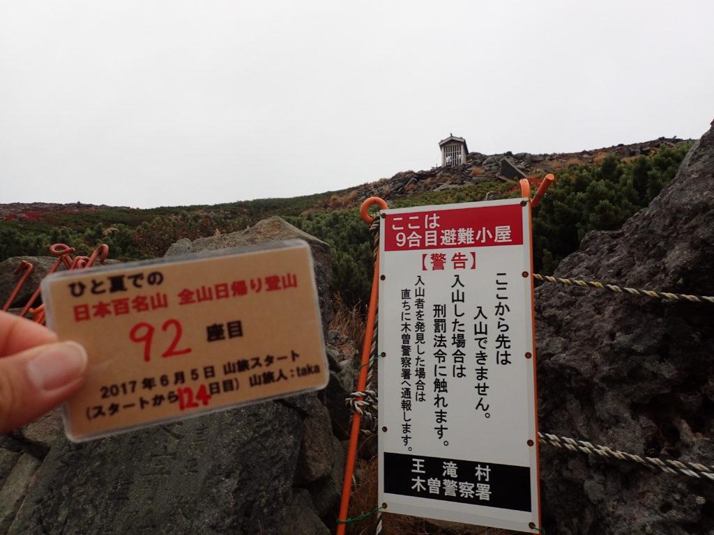 ひと夏での日本百名山全山日帰り登山で登った御嶽山の最高到達点で自作の登頂カードで記念写真