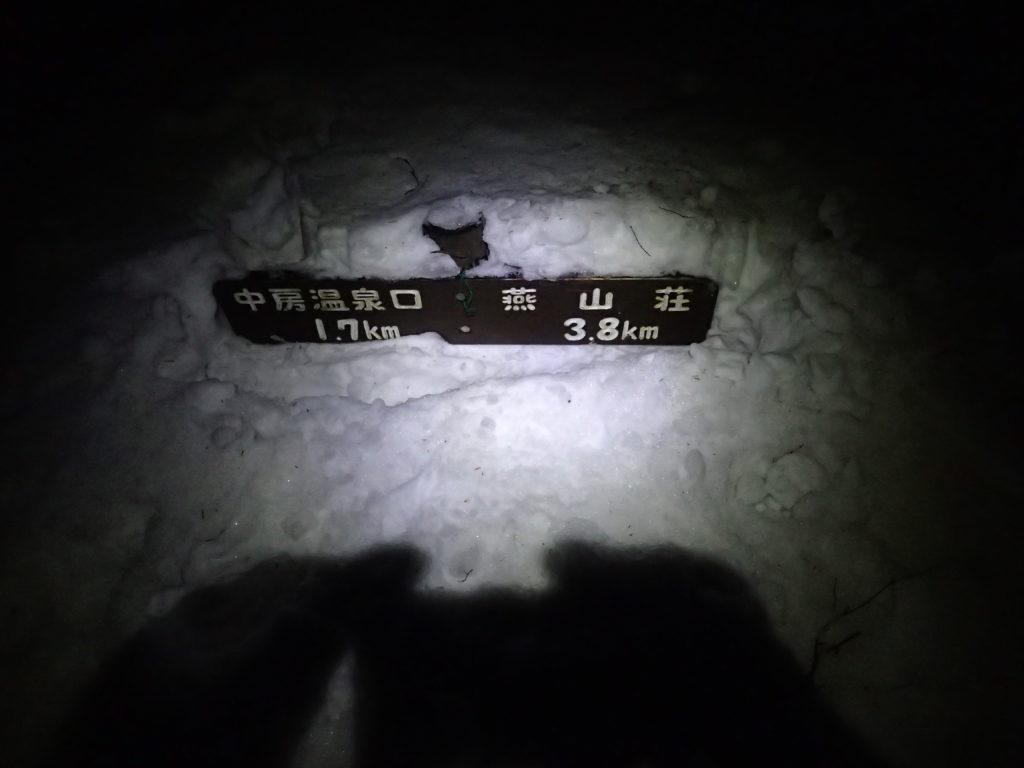 暗闇の合戦尾根で雪に埋まった道標をブラックダイヤモンドの登山用ヘッドライトであるストームの灯りで照らす。