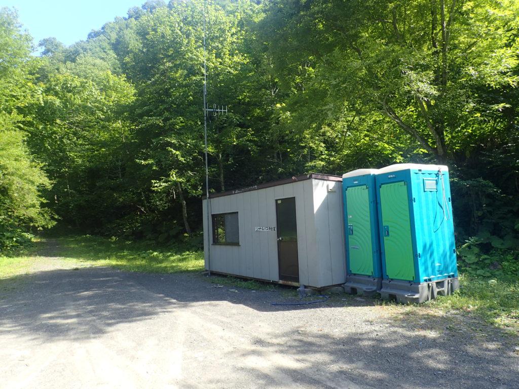 幌尻岳の振内コースの林道第二ゲートバス停留場のプレハブと仮設トイレ