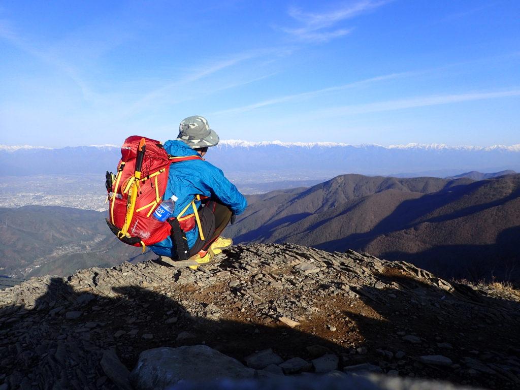 美ヶ原の王ヶ鼻で北アルプスを背景にモンベルの登山用レインウェアであるトレントフライーを着て記念撮影