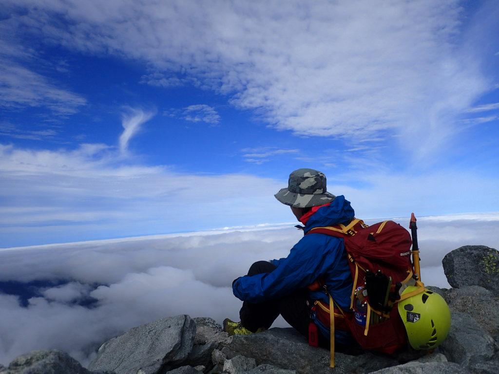 北アルプスの槍ヶ岳山頂でモンベルの登山用レインウェアであるトレントフライヤージャケットを着て記念撮影