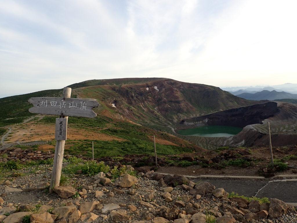蔵王山の刈田岳山頂の看板と御釜と熊野岳山頂方面