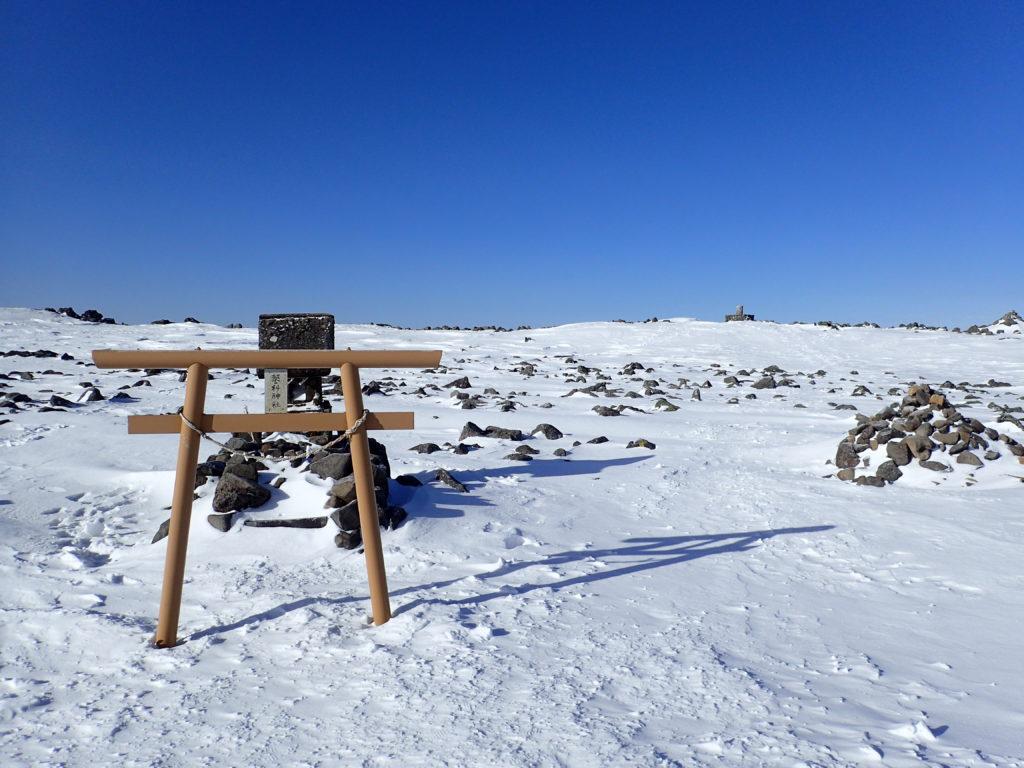 冬の蓼科山山頂の蓼科神社と方位盤