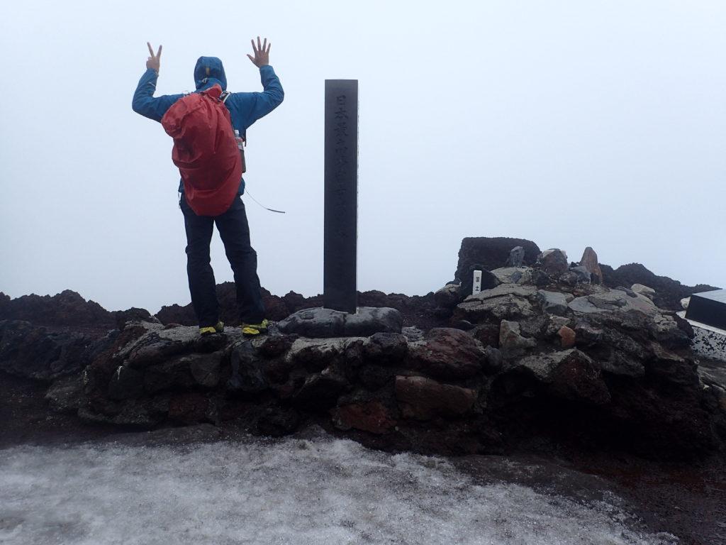 暴風の富士山でモンベルの登山用レインウェアであるトレントフライヤーを着て記念撮影