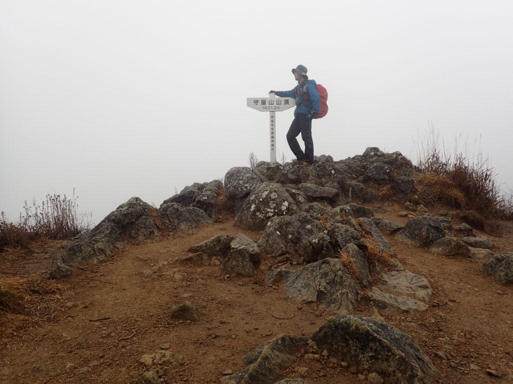 雨の守屋山東峰山頂でモンベルの登山用レインウェアであるトレントフライヤーを着て記念撮影
