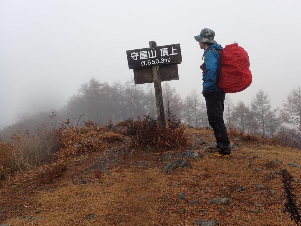 雨の守屋山山頂でモンベルの登山用レインウェアであるトレントフライヤーを着て記念撮影