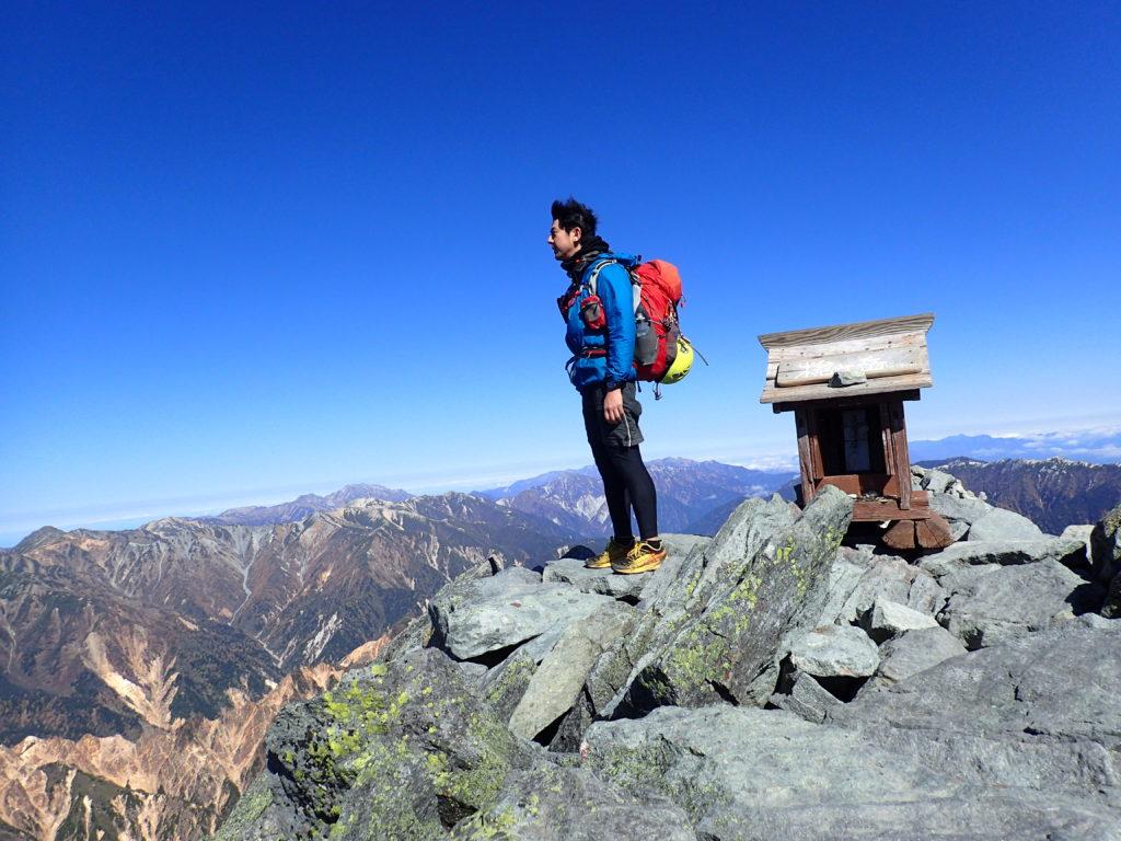 10月下旬の低温の槍ヶ岳山頂でモンベルの登山用レインウェアであるトレントフライヤーを着て記念撮影