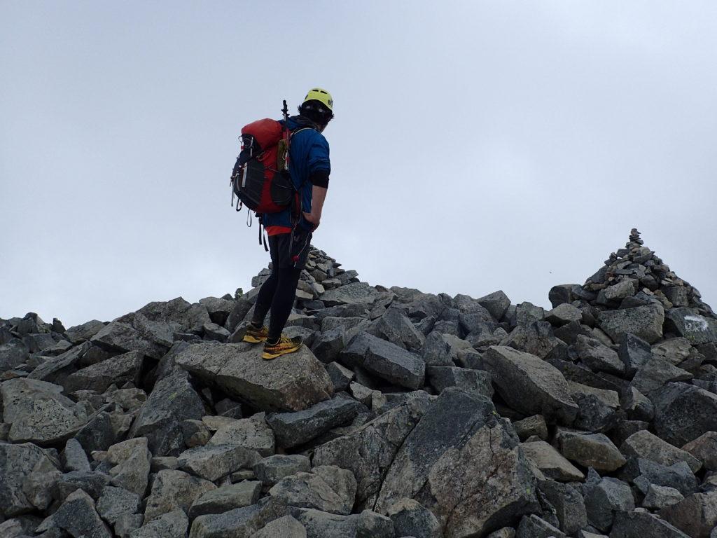 雨上がりの前穂高岳山頂でモンベルの登山用レインウェアであるトレントフライヤーを着て記念撮影