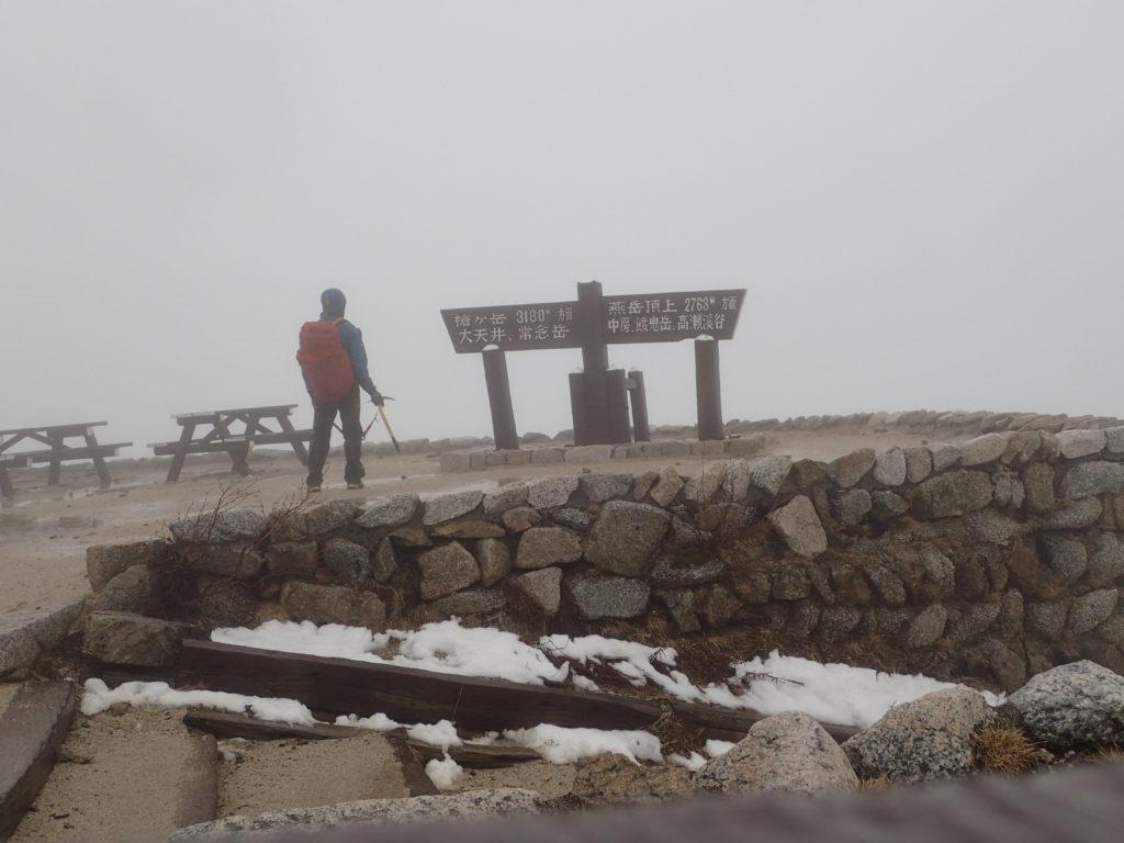 大雨の燕岳の燕山荘前でモンベルの登山用レインウェアであるトレントフライヤーを着ての記念撮影