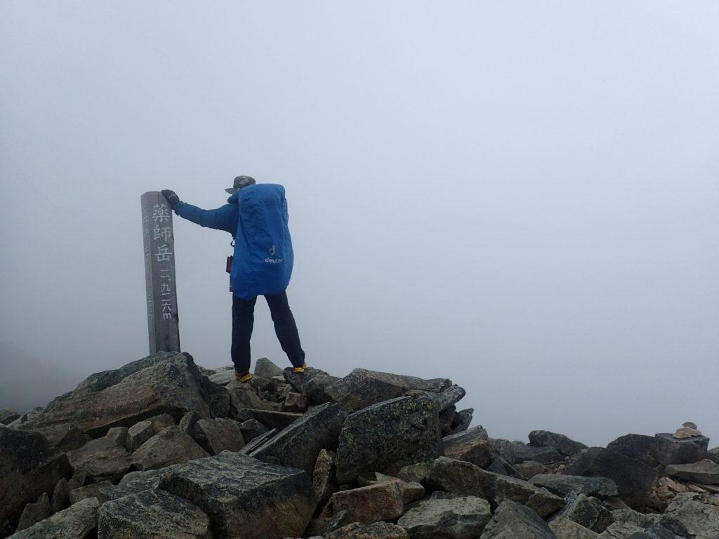 雨の薬師岳山頂でモンベルの登山用レインウェアであるトレントフライヤーを着て記念撮影