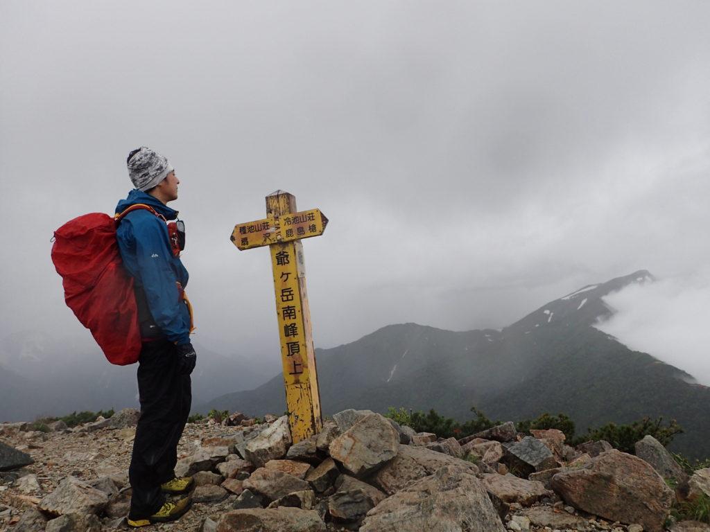 雨の爺ヶ岳山頂でモンベルの登山用レインウェアであるトレントフライヤーを着て記念撮影