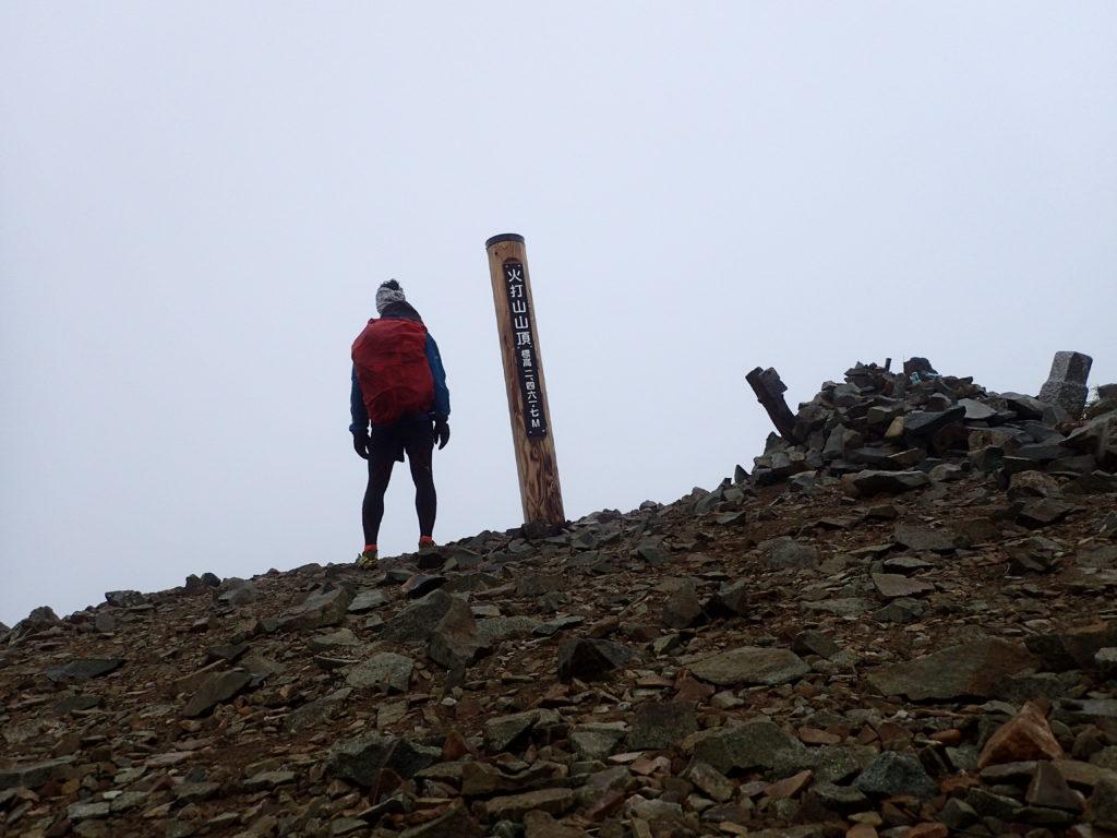 雨の火打山山頂でモンベルの登山用レインウェアであるトレントフライヤーを着て記念撮影