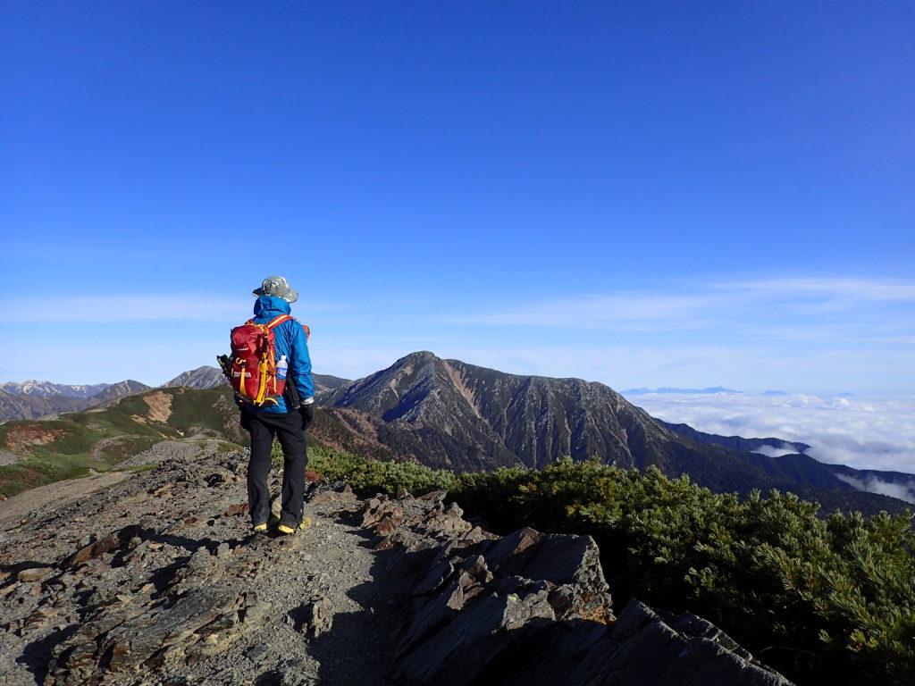 蝶ヶ岳の稜線から常念岳を背景にモンベルのレインウエアであるトレントフライヤージャケットを着て記念撮影