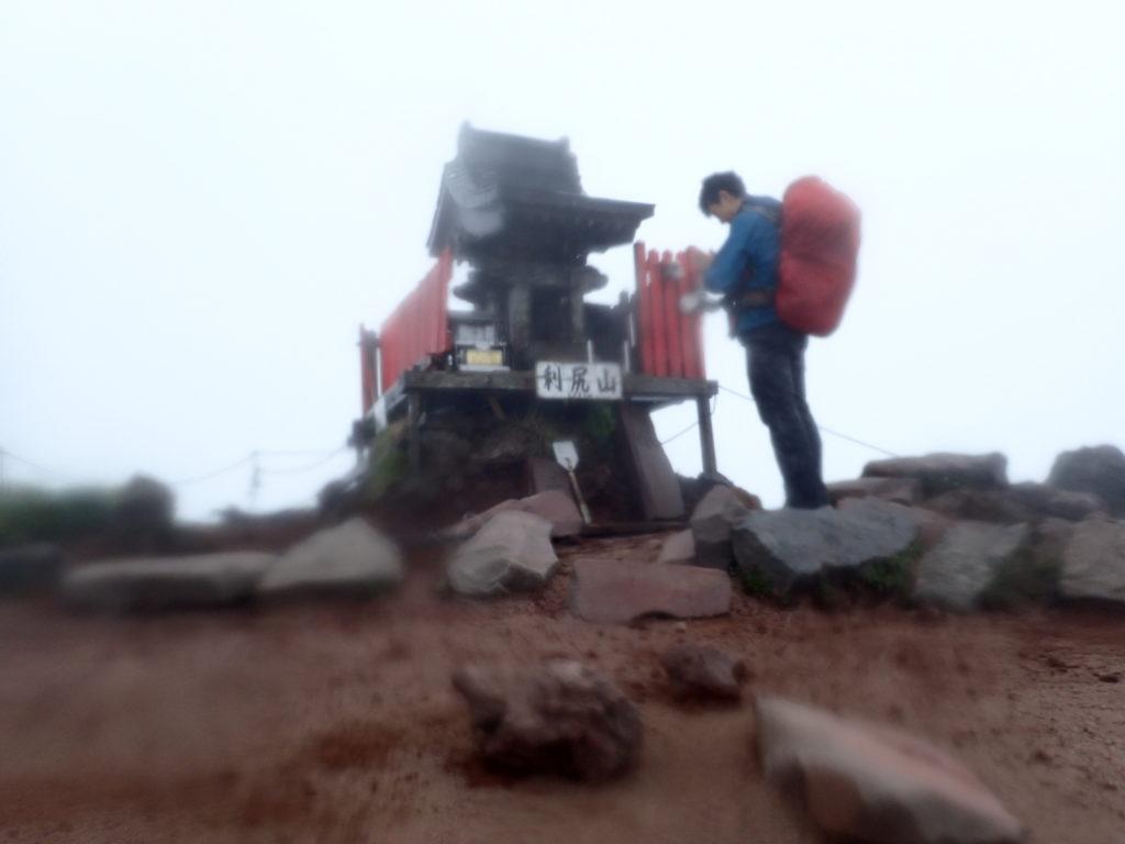 雨の降る北海道の利尻山の山頂でモンベルの登山用レインウェアであるトレントフライヤーを着て記念撮影