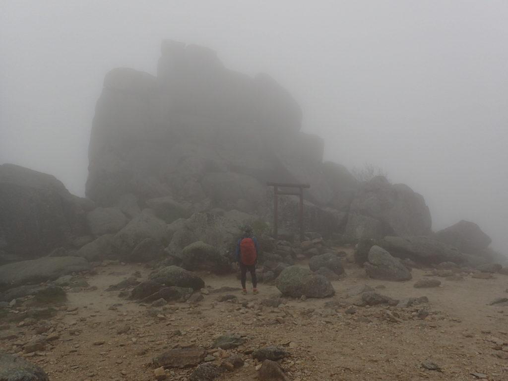 雨の金峰山の五丈岩の前でモンベルの登山用レインウェアであるトレントフライヤーを着て記念撮影