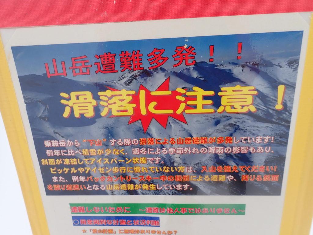 冬の乗鞍岳下山時の滑落のリスクを周知する看板