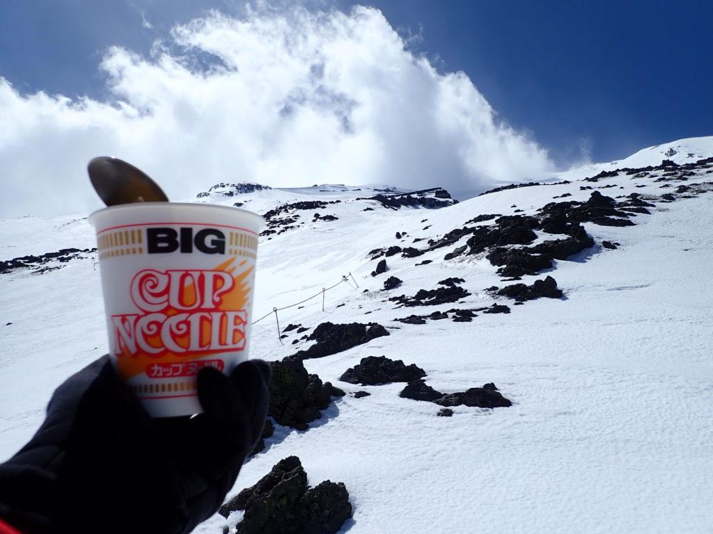 残雪期の富士山で山頂方向を見上げながらのカップラーメン