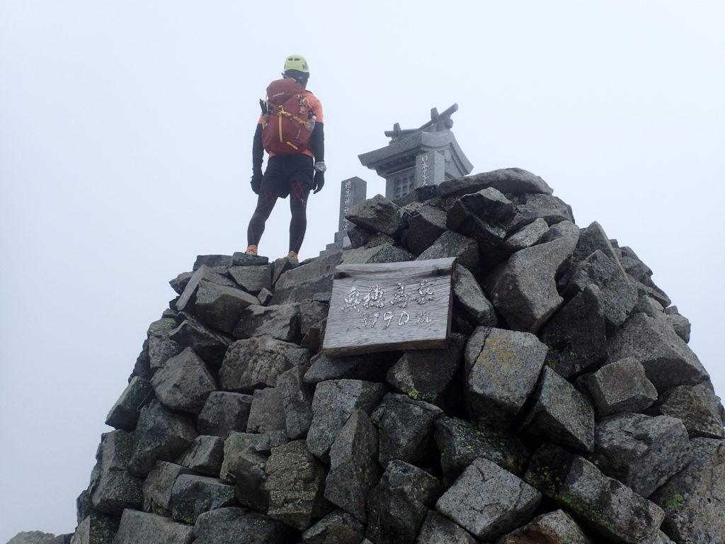 奥穂高岳の山頂でモンベルの登山用ザックであるバーサライトパックを背負って記念撮影