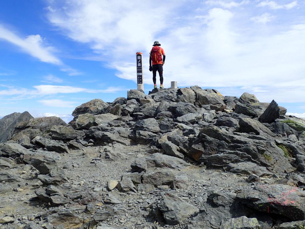 日本百名山である間ノ岳山頂に立つ背中にモンベルの登山用ザックであるバーサライトパック