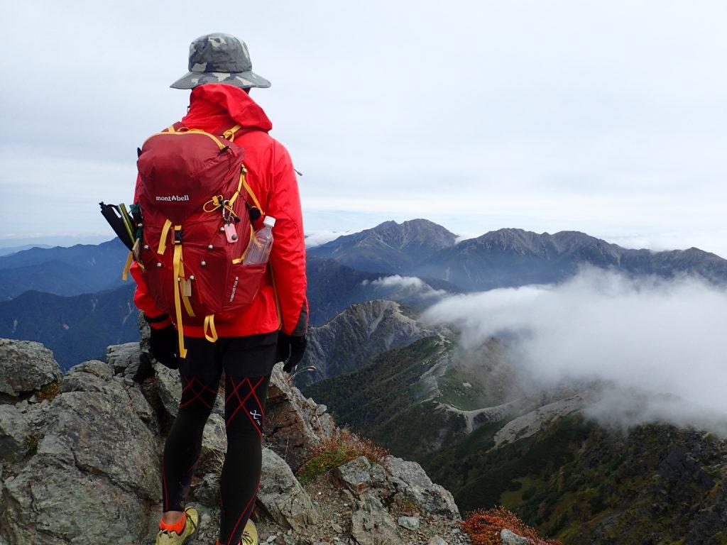 塩見岳の稜線から北岳と間ノ岳を眺める背中にモンベルの登山用ザックであるバーサライトパック