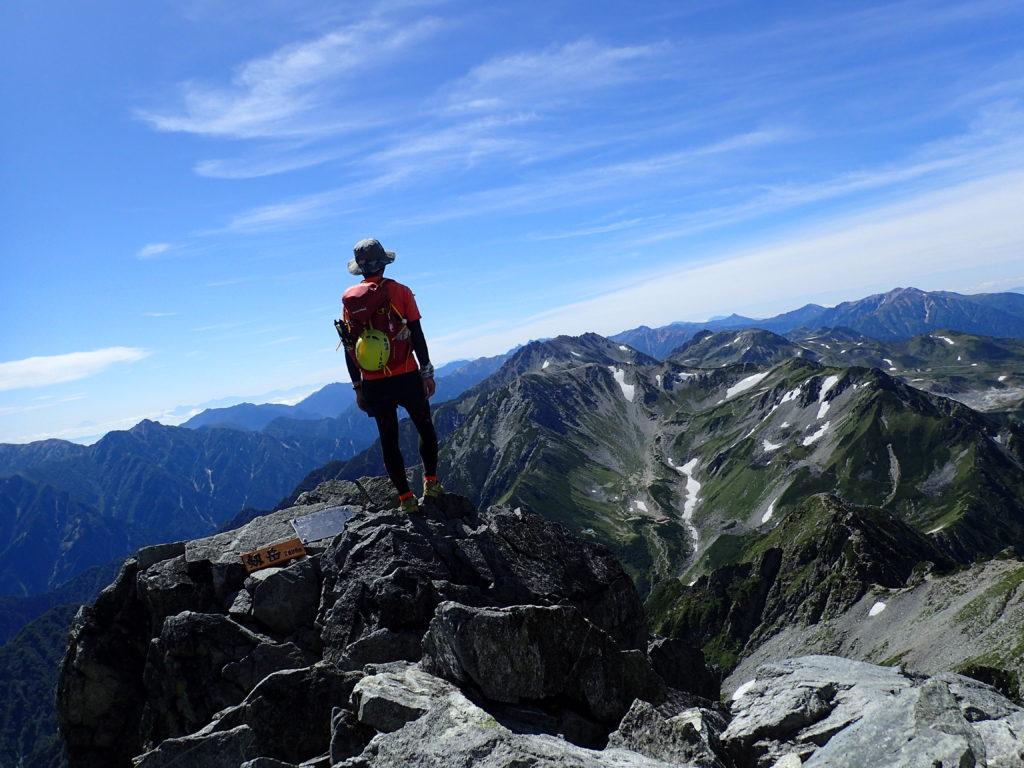 剱岳山頂に立つ背中にモンベルの登山用ザックであるバーサライトパック